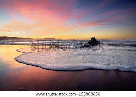 wave foam on beach sand at sunset - stock photo
