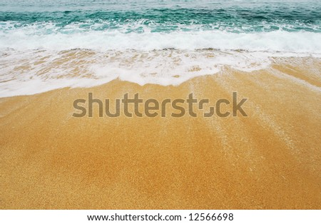 Wave gently washing onto the sand - stock photo