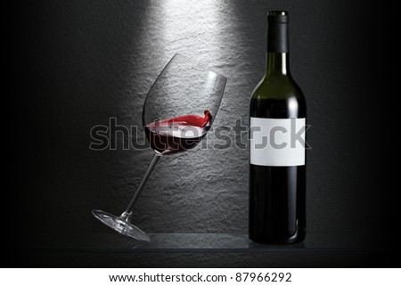 Wave in a tilting wine glass beside a bottle - stock photo