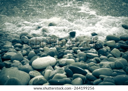 Wave is transformed into foam on a pebble beach in Cyprus. Shallow depth of field - stock photo