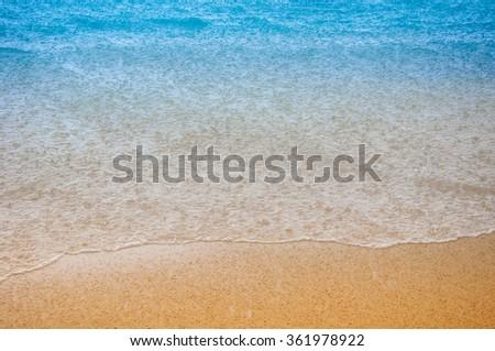Wave of the sea on the sand beach at rain - stock photo