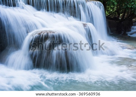 Wave of waterfall. The Kuang Si Falls, sometimes spelled Kuang Xi, is a three tier waterfall about 29 kilometers (18 mi) south of Luang Prabang in Laos Asia - stock photo