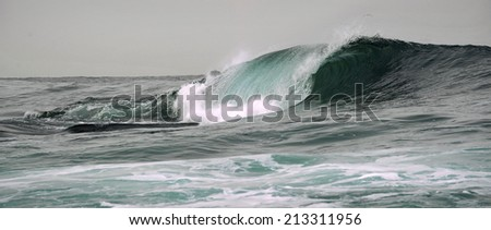 Wave on the surface of the ocean. Wave breaks on a shallow bank - stock photo