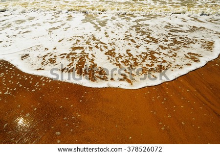 Wave rolls on the warm golden sandy beach in a summer sunny day close-up - stock photo