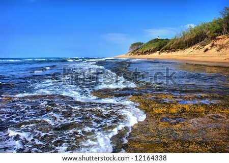 Wave runs on beach next to coral reef. Shot in Sodwana Bay Nature Reserve, KwaZulu-Natal province, Southern Mozambique area, South Africa. - stock photo