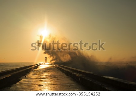 Wave splash at sunset near lighthouse, Porto, Portugal  - stock photo