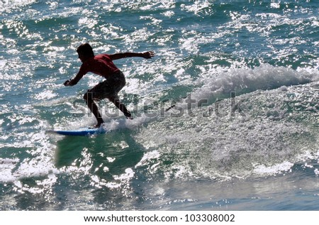 Wave surfer surfing wave at sea. - stock photo