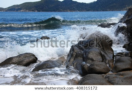waves and stones at the blue Ionian sea seaside in Greece
