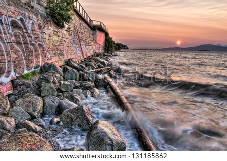 Waves and sunset with Graffiti on wall - stock photo