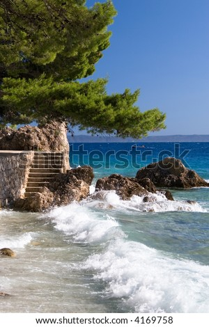 Waves at the rocks in the blue sea of Brela Croatia