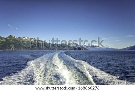 Waves behind cruise ship over Mountains near Seward, Alaska, USA - stock photo