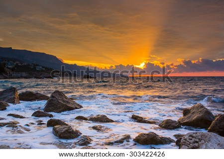 Waves break about stones at sunrise over the sea - stock photo