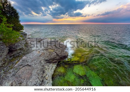 Waves break at dawn on the rocky coastline of Door County, Wisconsin's Cave Point. - stock photo