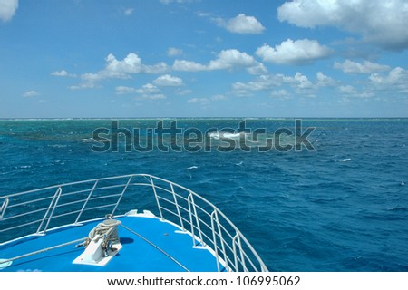 Waves break on the reef under blue sky on a live aboard on the Great Barrier Reef, Australia - stock photo