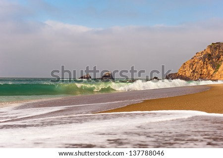 Waves breaking along the shoreline of a small cove in Laguna Beach, California. - stock photo
