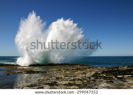 Waves breaking on a rock on the coast, South Island of New Zealand - stock photo
