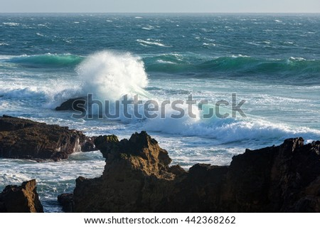 Waves breaking on rocky coast.  Evening seascape view from shore. - stock photo