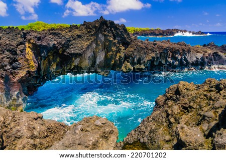 Waves breaking on the rocks on a sunny day during a spectacular ocean view on the Road to Hana, Maui, Hawaii, USA - stock photo