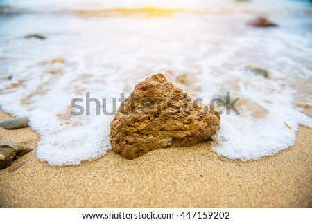 Waves breaking on the rocks on the beach at sunset - stock photo