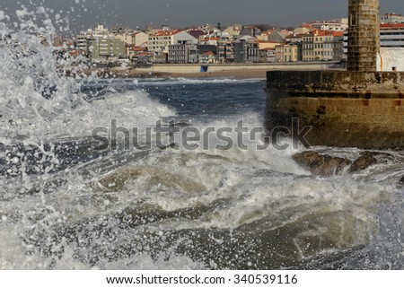 Waves breaking violently against rocks and pier of the Douro river mouth, seeing in background part of coastal town of Porto in a stormy but sunny morning - stock photo