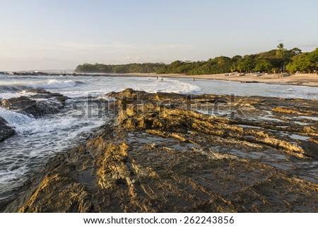 Waves crash on the rocky shore on Playa Pelada on the Pacific Coast of Costa Rica. - stock photo