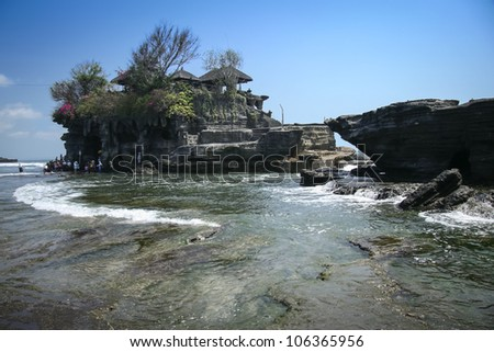 waves crashing around the sea temple of tanah lot built on a rocky outcrop of the coast of bali indonesia - stock photo