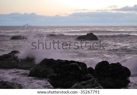 Waves crashing in the sunset - stock photo