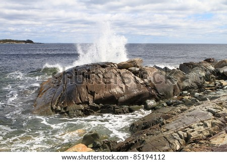 Waves crashing into a rocky coastline - stock photo