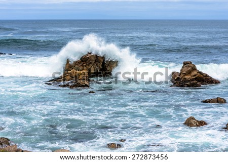 waves crashing on rock and geological formations along the rugged Big Sur coastline, near Monterey, CA. on the California Central Coast - stock photo