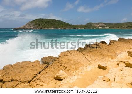 Waves Crashing on Rocky Limestone Coastline at Half Moon Bay Antigua - stock photo