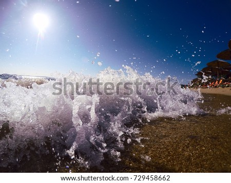Waves crashing on sand beach, sun light on blue sky in background , summer travel vacation.