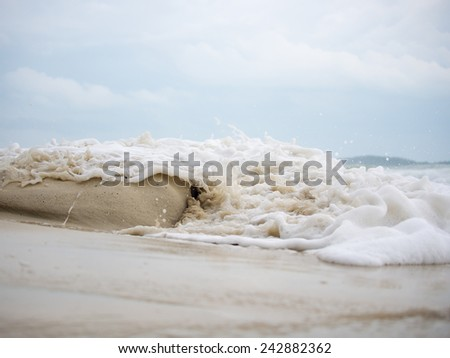 Waves crashing on the sand at the beach - stock photo