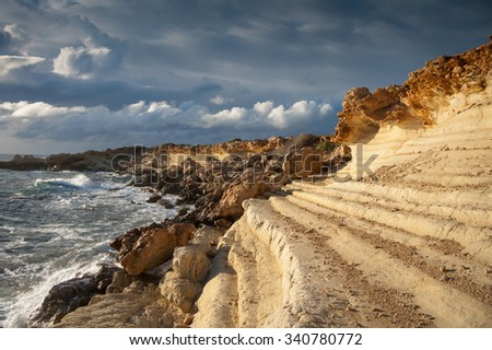 waves crashing on the yellow rocks, sun and strong clouds before the raine - stock photo