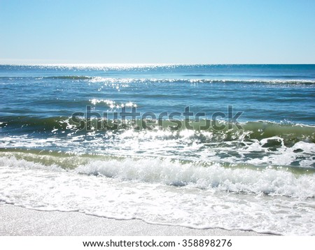 waves crashing onto the sandy shore - stock photo