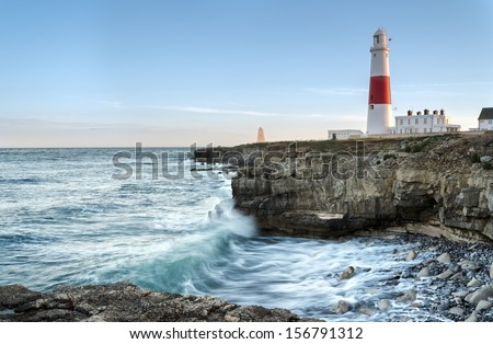 Waves crashing over rocks at Portland Bill lighthouse on the Jurassic Coast in Dorset - stock photo