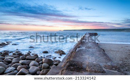 Waves crashing over the harbour wall at Sennen Cove near Land's End in Cornwall - stock photo