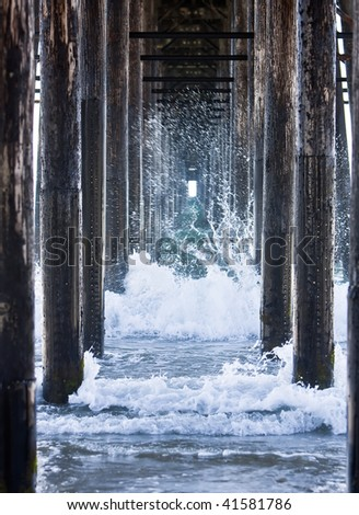 Waves crashing underneath a pier while the tide is rolling out. - stock photo