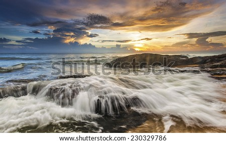 Waves Flow Hit the Rock During Sunrise - stock photo