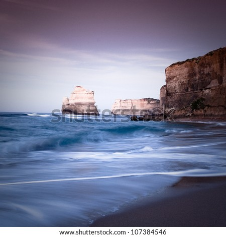 Waves formation with foam at sand level of Gibson Steps with cliff on one side looking, Twelve Apostle, Australia - stock photo