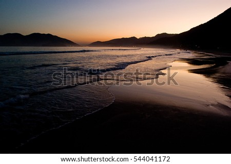 Waves in sunrise beach with mountains in the background