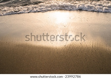 Waves make a lovely pattern on a beach, at sunset. - stock photo
