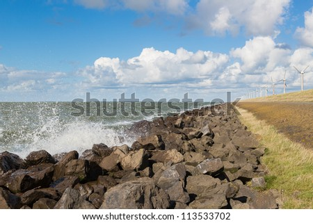 Waves near a Dutch breakwater with Wind turbines - stock photo