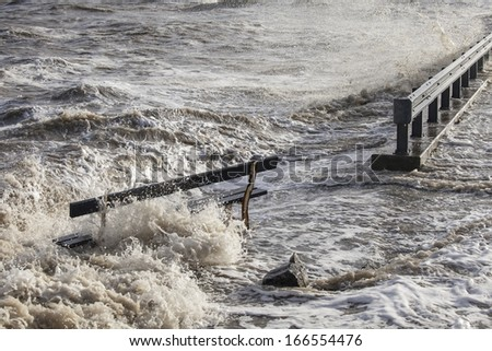 Waves of ocean water surrounding a wooden bench after heavy rains and storm in a coastal town in the Netherlands - stock photo