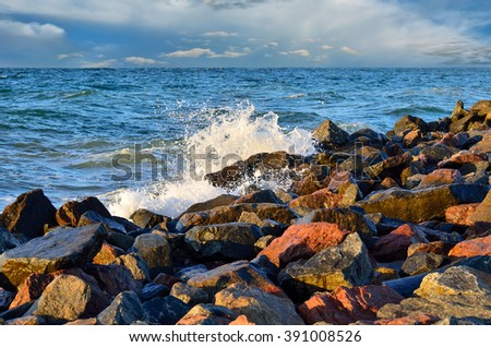 Waves of the sea among the rocks on the beach - stock photo