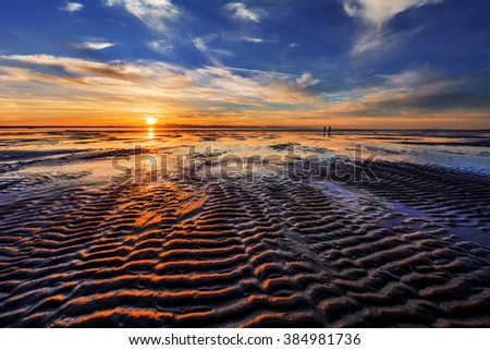 Waves on the sand, two people walking along the beach, low sunset brightens the landscape - stock photo
