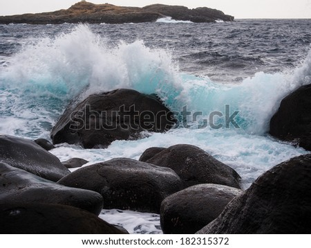 Waves on the sea crashing against rocky shore - stock photo