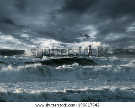 Waves over a lighthouse against stormy clouds. Enhanced sky. Toned blue. - stock photo