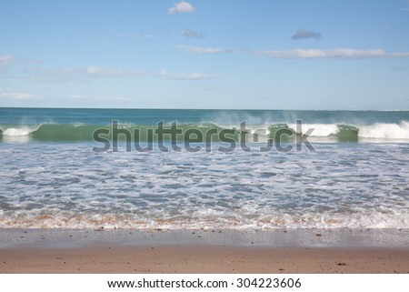 waves rolling into shore, clear sunny day at a sandy surf beach, Gisborne, North Island, New Zealand  - stock photo