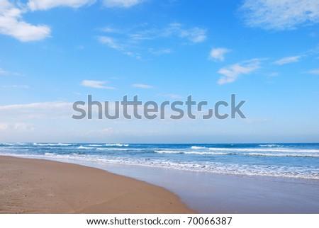 Waves running on sandy coast of Mediterranean sea - stock photo