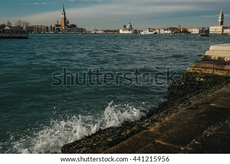 Waves smash of a stone berth in the front of a beautiful old cityscape - stock photo